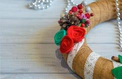A grinalda e a fita do Natal curvam-se em um fundo da placa de madeira Foto de Stock