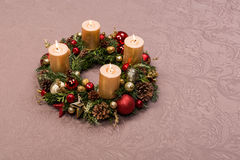 Grinalda feito a mão fresca do Natal decorada com vermelho e decorações do Natal do ouro, abeto-cones e nozes com velas do ouro Foto de Stock Royalty Free