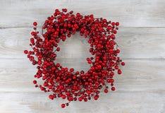 Grinalda vermelha do feriado da baga em placas de madeira brancas rústicas Fotos de Stock Royalty Free
