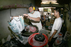 Grind meat. Traders who have been ordered by the buyer at a traditional market in the city of Solo, Central Java, Indonesia Stock Photos