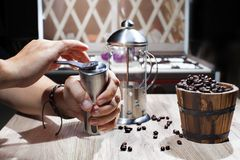 Grind the roasted coffee beans with a manual coffee grinder. royalty free stock images