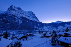 Grindelwald village at dusk with Mt. Eiger peak in the background, snow covered landscape in winter, Switzerland stock photos