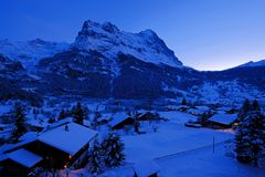 Grindelwald village at dusk with Mt. Eiger peak in the background, snow covered landscape in winter, Switzerland royalty free stock images