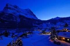 Grindelwald village at dusk with Mt. Eiger peak in the background, snow covered landscape in winter, Switzerland royalty free stock photos