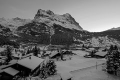 Grindelwald village at dusk with Mt. Eiger peak, snow covered landscape in winter, black white photography, Switzerland royalty free stock image