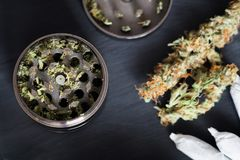 Grinder for chopping weed cannabis and a flower of marijuana on a black background surrounded by joint royalty free stock image