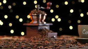 Grinder filled with coffee beans and cup on a saucer stock footage
