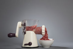 Grinder processing minced meat. Household meat grinder with some minced meat coming out into a bowl Stock Photo