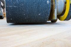 Grinder with the sandpaper on the drum front view standing on the recently laid floor and ready-polishing and perfectly flat surfa. Ce flooring stock image