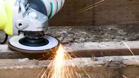 Grinder shoots sparks out as it cuts through heavy nail. In wood stock video
