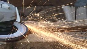 Grinder shoots sparks out as it shaves through heavy nail. Grinder shoots sparks out as it cuts through heavy nail in wood stock footage