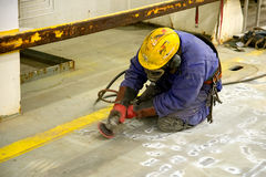 Grinder. Surface preparation for painting the ship by shipyard worker grinder Stock Photo