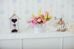 Grinder and a vase of spring flowers in the style Shabby chic Stock Photo