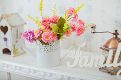 Grinder and a vase of spring flowers in the style Shabby chic Stock Image