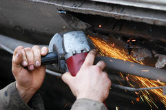 Grinder at work. Close-up image of grinders hands and his tool while working, you can see sparks, too Stock Photo