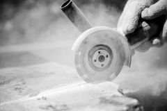 Grinder worker cuts a stone Stock Images