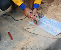 Grinder worker cuts a stone the electric tool worker is tiling a Stock Image