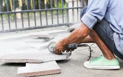 Grinder worker cuts a stone tile Stock Photos