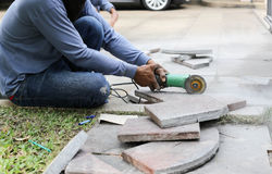 Grinder worker cuts a stone tile Royalty Free Stock Images