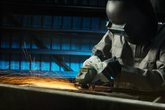 Grinding. Man grinding in workshop with safety precaution Royalty Free Stock Photo