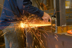 Grinding. With a grinder on steel making yellow/orange sparks sprayi around the area stock images