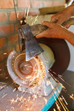 Grinding bench axe using a grinding machine. Close up Stock Photo