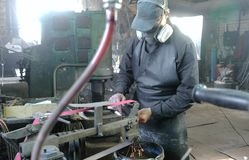 Grinding billets of metal knife on a belt-grinding machine. Worker performs his job in a protective mask on his face in. The shop among the equipment Stock Image