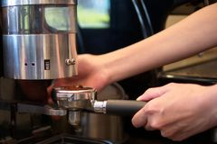 Grinding Coffee Beans. Barista grinding coffee beans by machine. Close up and Selective focus stock photography