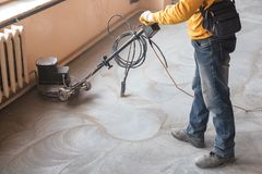 Grinding of concrete floor. Workers grind the concrete floor at the construction site stock image