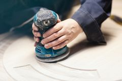 Grinding the door with a grinding machine. Hands with a grinder close up. No face. Door finish stock photography