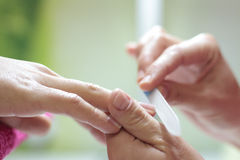Grinding down a fingernail with a nail file Royalty Free Stock Photography