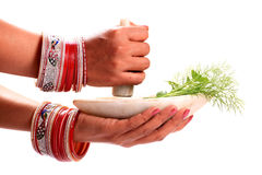 Grinding green herbs. Female hands grinding green herbs in stone mortar Royalty Free Stock Photo