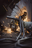 Grinding loops of steel pipe with many sparks on a work table. HVertical photo stock images
