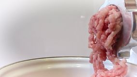 Grinding meat with an electric meat grinder. Minced meat climbs from a meat grinder. stock video footage
