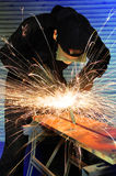 Grinding metal. Factory worker creating sparks whilst grinding metal Stock Photo