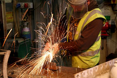 Grinding Metal. A workman grinding metal in preparation for welding Royalty Free Stock Photo