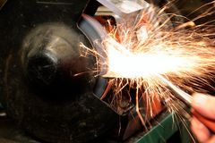 Grinding metal with a grinder in a workshop Royalty Free Stock Image