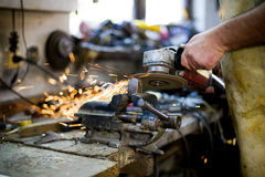 Grinding metal part. In work shop Stock Image