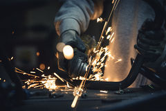 Grinding metal pipe in a workshop and sparks flying Stock Image