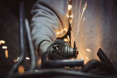 Grinding metal pipe in a workshop and sparks flying. Horizontal photo Stock Images