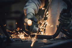 Grinding metal. Steel pipe cutting with flash of sparks close up Royalty Free Stock Photography