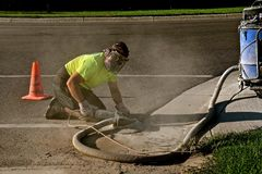 Grinding ragged concrete edge along a road and curb. An unidentified construction worker wearing safety breathing equipment is grinding down the concrete edge on Stock Photography