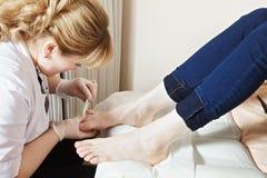 Grinding toenails process. Grinding toenails with file process. Horizontal shot Royalty Free Stock Photography