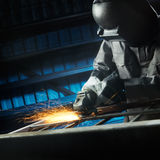 Grinding after weld. Man grinding in workshop with safety precaution Stock Photo