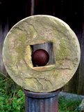 Grindstone with cannonball. Antique cannon ball sitting inside of a grindstone on an old pedistal Stock Photography