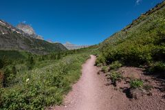 Grinnell Glacier Trail Cuts Through Green Valley on blue sky day royalty free stock photos