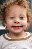 Grinning 2 yr old blond boy who lost a front tooth. A grinning smiling happy two year old little boy with curly blond hair who has lost a front tooth. Dentist's Stock Images