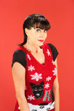 Grinning adult female in ugly Christmas sweater. Front view on grinning woman wearing ugly Christmas sweater over red background Royalty Free Stock Images