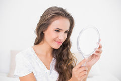 Grinning attractive brunette looking at mirror Stock Photography