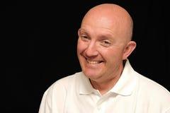 Grinning bald man. Portrait of grinning bald man, black background stock image